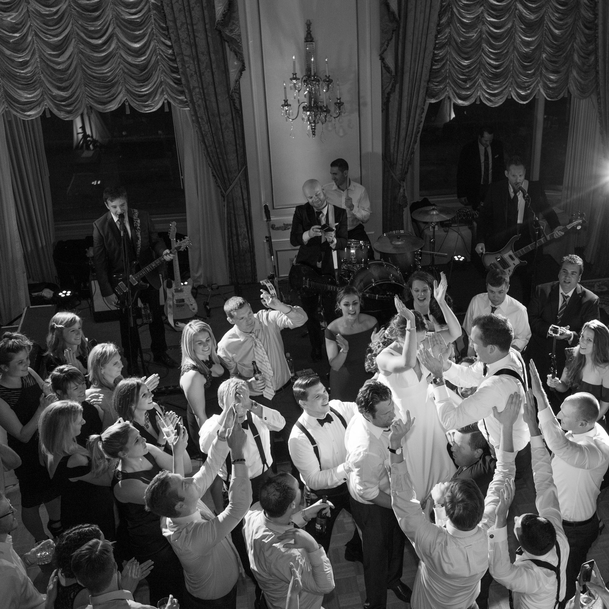 black and white image of bride and groom on crowd's shoulders in ballroom from above
